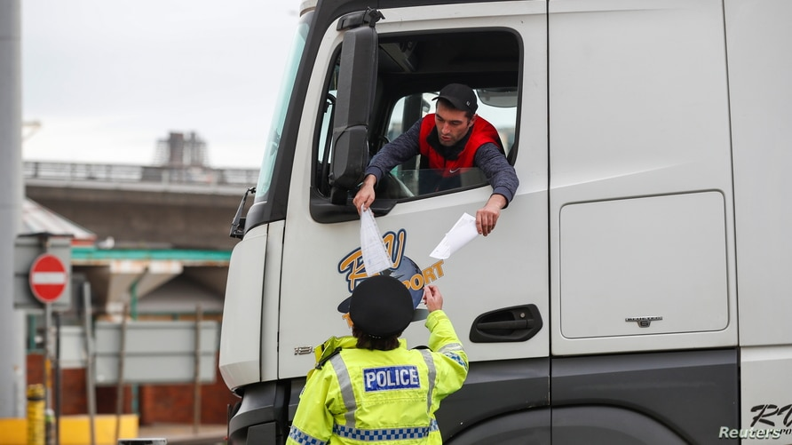 A lorry driver shows the papers for a police officer at the entrance of the Port of Dover, as EU countries impose a travel ban…