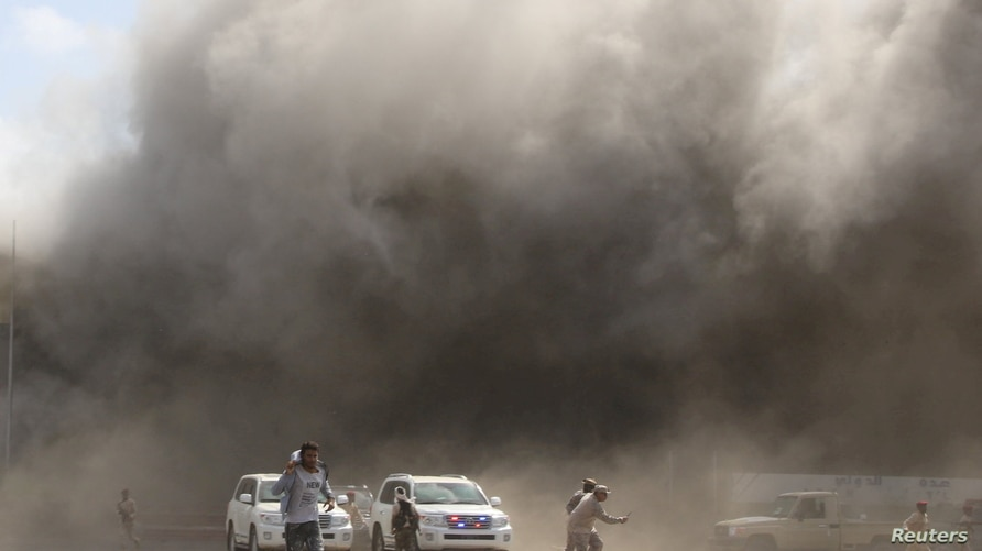 People react as dust rises after explosions hit Aden airport, upon the arrival of the newly-formed Yemeni government in Aden,…
