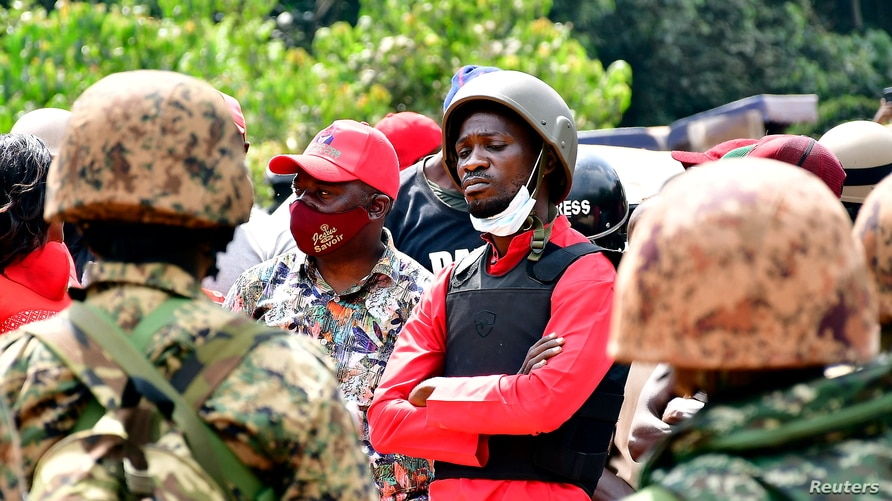 Ugandan opposition presidential candidate Robert Kyagulanyi, also known as Bobi Wine (C), is escorted by policemen during his…