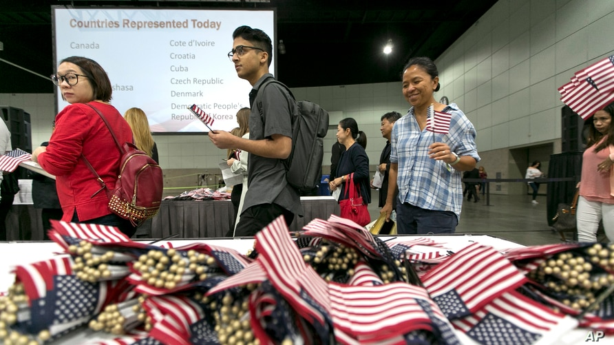 FILE - Immigrants pick flags as they arrive to take their citizenship oath during naturalization ceremonies in Los Angeles.