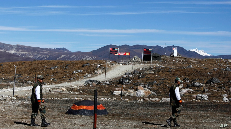 FILE - In this Sunday, Oct. 21, 2012, file photo, Indian army soldiers walk along the line of control at the India- China…