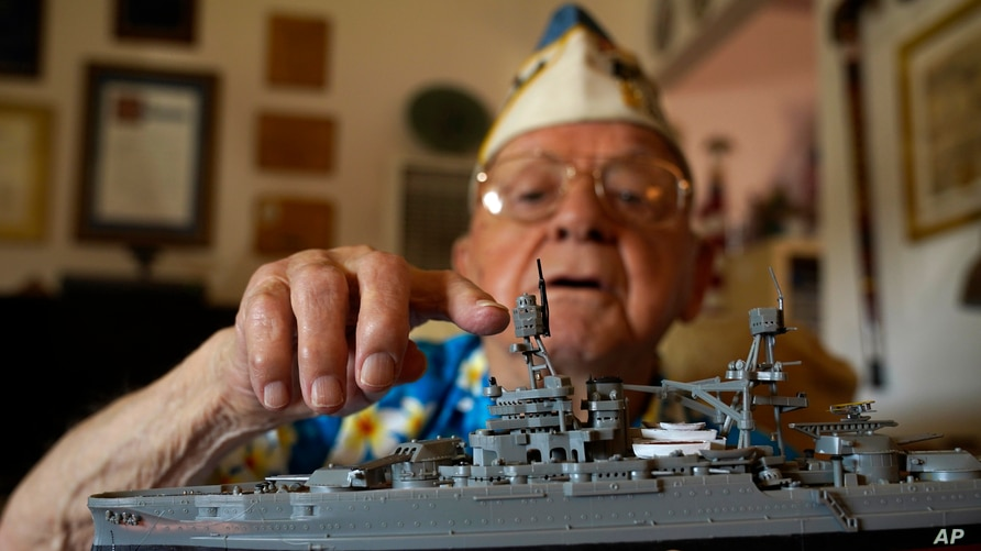 Mickey Ganitch holds up a model of the USS Pennsylvania and points to where he served as a lookout during the 1941 attack.