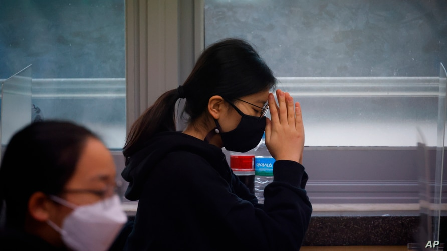A student  wearing a face mask prays before the start of the annual college entrance examination