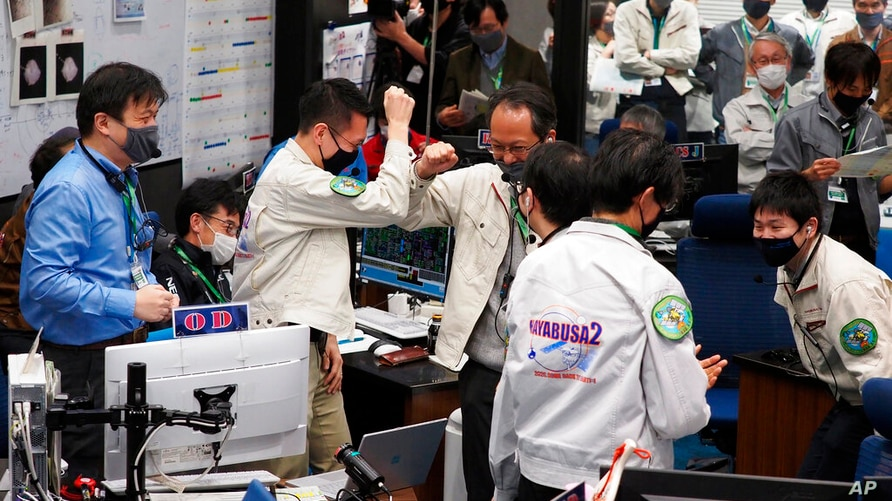 Project members celebrate as the success of trajectory control maneuver to withdraw from the Earth's sphere is confirmed, at a…