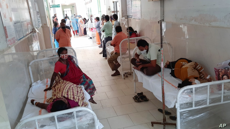 Patients and their bystanders are seen at the district government hospital in Eluru, Andhra Pradesh state, India, Sunday, Dec.6…
