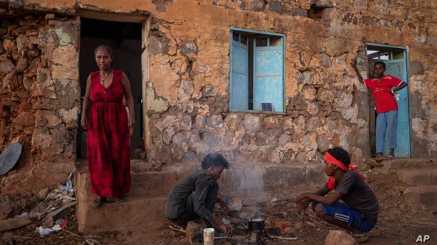 Tigrayans who fled the conflict in Ethiopia's Tigray region, start wood fires to prepare dinner, in front of their shelter.