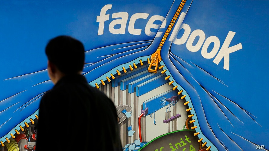 FILE - In this June 11, 2014, file photo, a man walks past a mural in an office on the Facebook campus in Menlo Park, Calif…