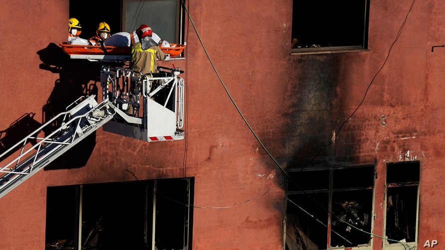 Firefighters load the body of a dead person into a crane after a fire on a building in Badalona, Barcelona, Spain, Dec. 10, 2020.