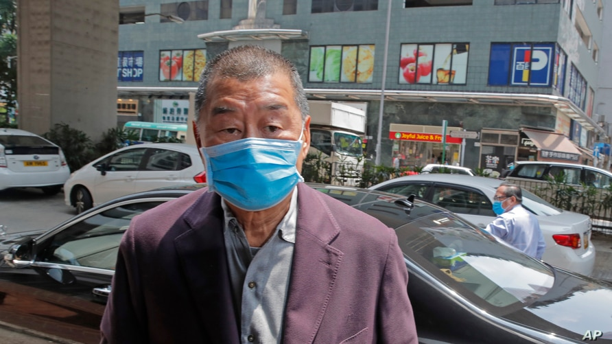 FILE - Pro-democracy media tycoon Jimmy Lai arrives at a police station in Hong Kong.
