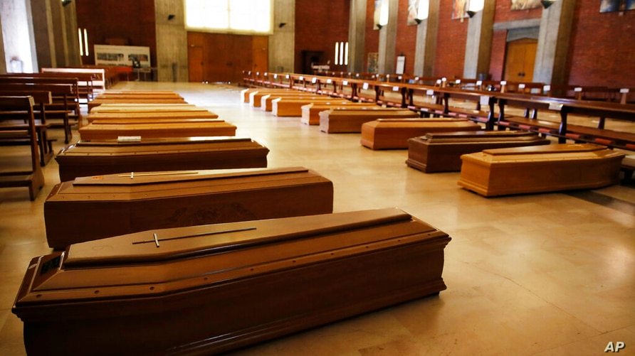 FILE - In this March 26, 2020 file photo, coffins are lined up on the floor in the San Giuseppe church in Seriate, one of the…