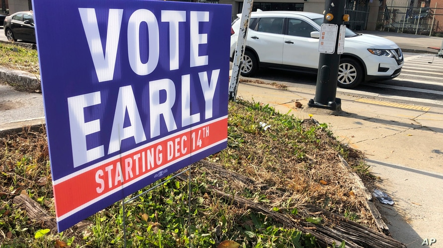 A sign in an Atlanta neighborhood on Friday, Dec. 11, 2020, urges people to vote early in Georgia's two U.S. Senate races. The…
