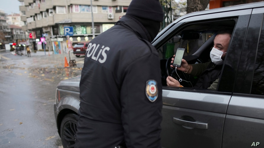 A man wearing a mask to help protect against the spread of coronavirus, shows a document as a police officer checks IDs during…