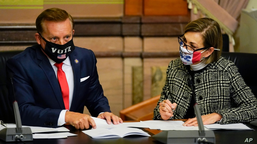 Iowa Secretary of State Paul Pate, left, and Iowa Gov. Kim Reynolds tally the votes cast by members of Iowa's Electoral College…