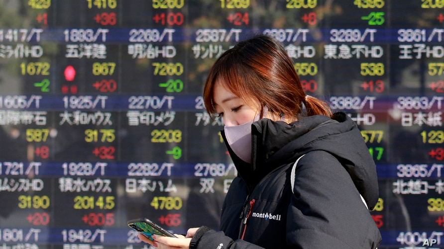 A woman walks by an electronic stock board of a securities firm in Tokyo, Dec. 16, 2020.