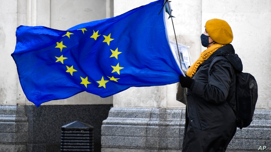 An anti Brexit demonstrator holds an EU flag in Parliament Square, in London, Wednesday, Dec. 16, 2020. Ursula von der Leyen said Wednesday she saw clear progress in the trade talks with the UK, turning a post-Brexit deal from a fleeting possibility into an ever more realistic possibility.(AP Photo/Alberto Pezzali)