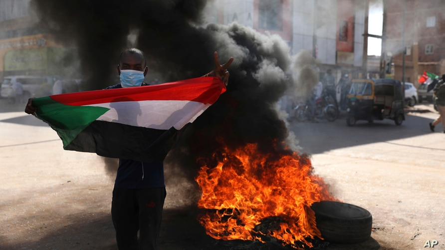 A demonstrator gives the victory sign during a protest, in Khartoum, Sudan, Dec. 19, 2020.