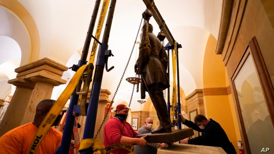 This Monday, Dec. 21, 2020 photo provided by the Office of the Governor of Virginia shows workers removing a statue of…