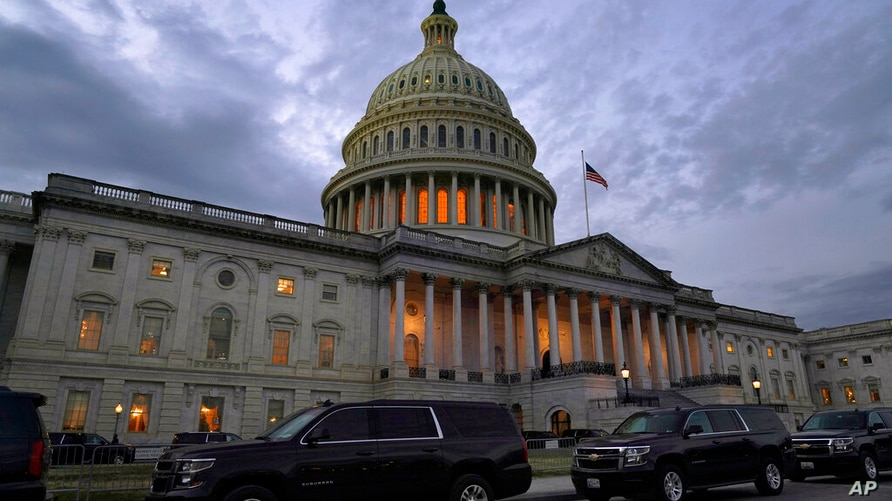 Dusk falls over the Capitol, Monday, Dec. 21, 2020, in Washington. Congressional leaders have hashed out a massive, year-end…