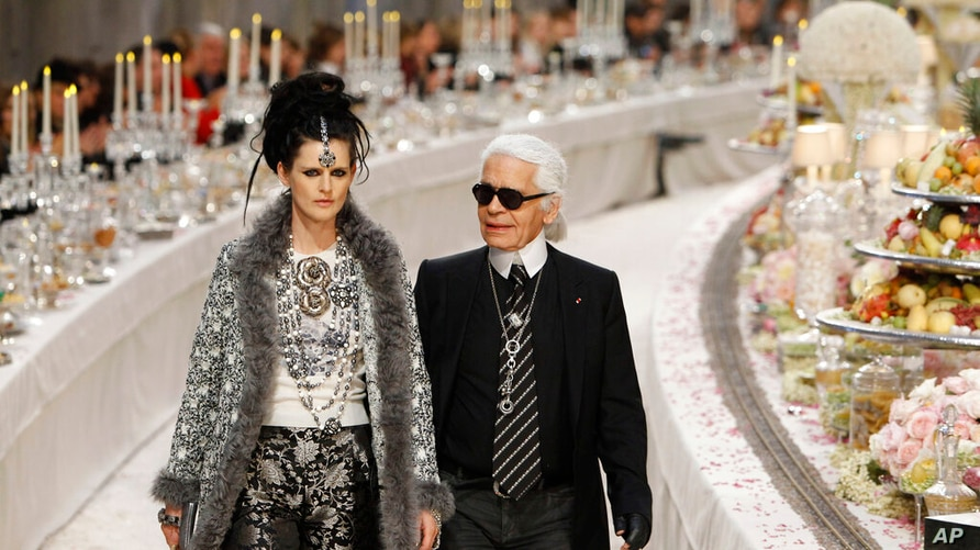 FILE - In this Tuesday, Dec. 6, 2011 file photo, German fashion designer Karl Lagerfeld with British model Stella Tennant, left…