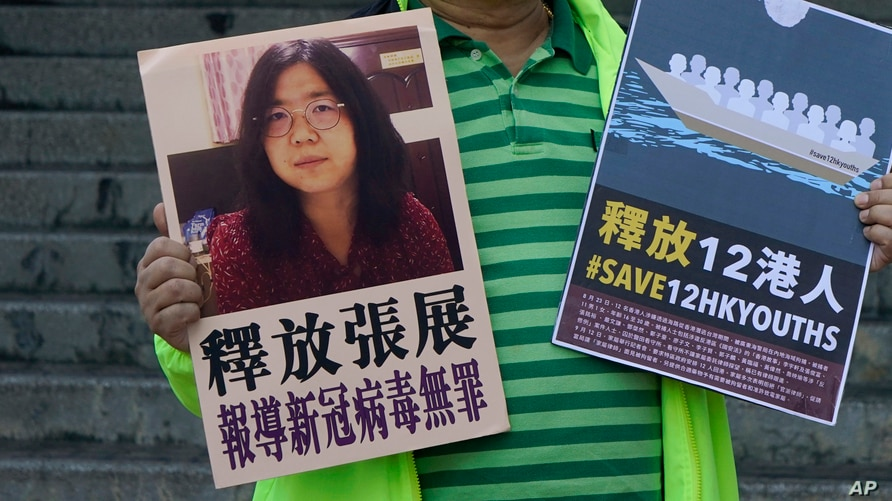 A pro-democracy activist holds placards with the picture of Chinese citizen journalist Zhang Zhan outside the Chinese central…