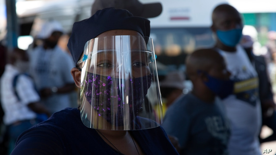 FILE — In this Thursday, Dec. 24, 2020 file photo people wear face masks to protect against COVID-19 before boarding a minibus…