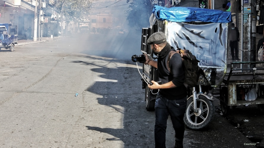 Rebaz Majeed takes photos on a street in Sulaymaniyah while covering anti-government protests on Dec. 3, 2020. (Courtesy, Hama Sur)