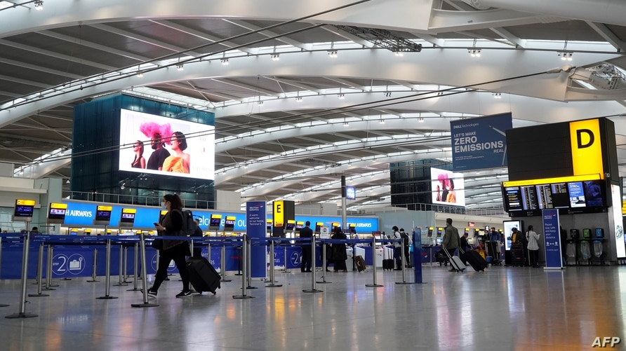 Travellers wearing face coverings walk with their luggage in the almost deserted departures hall at Terminal 5 of Heathrow…