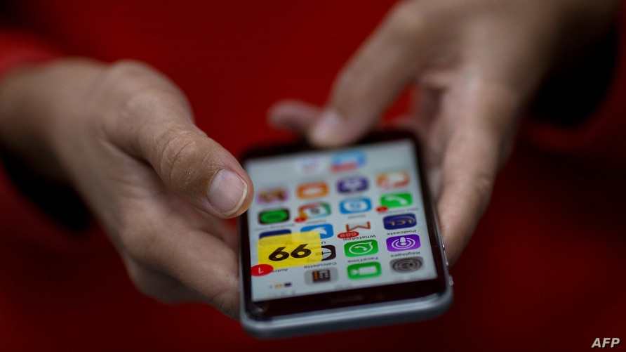 FILE - A woman holds a smartphone showing various apps, in Rio de Janeiro, Brazil, Jan. 4, 2018.