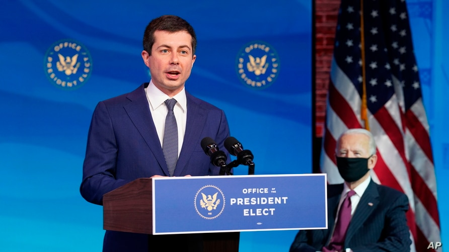 Former South Bend, Indiana, Mayor Pete Buttigieg, President-elect Joe Biden's nominee to be transportation secretary reacts to his nomination as Biden looks on during a news conference at The Queen theater in Wilmington, Delaware, Dec. 16, 2020.