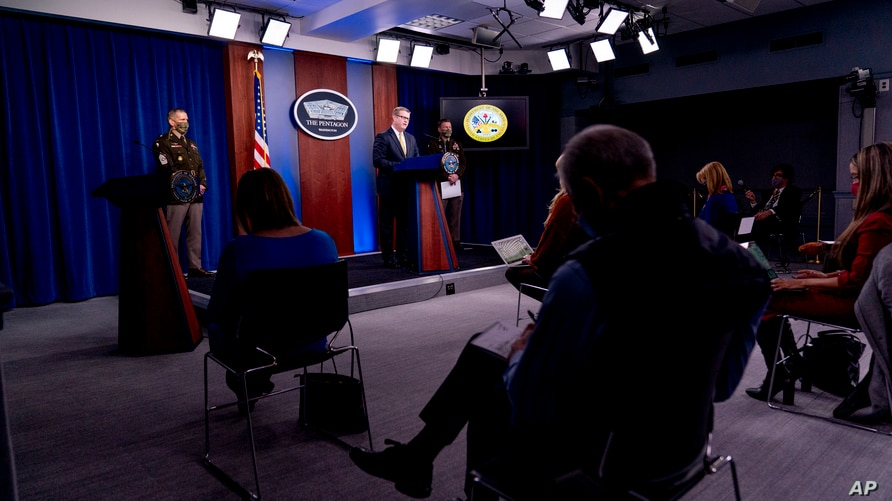 Secretary of the Army Ryan McCarthy, center, speaks at a briefing on an investigation of widespread problems at the U.S. Army base in Fort Hood, Texas, at the Pentagon, in Arlington, Virginia, Dec. 8, 2020.