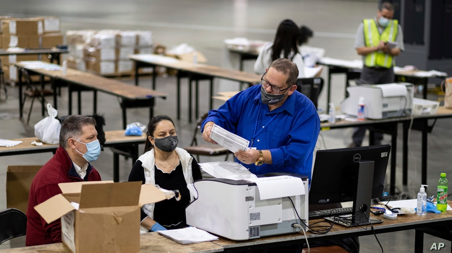 FILE - Election workers scan ballots during a recount of the presidential vote, at the Georgia World Congress Center, in Atlanta, Georgia, Nov. 25, 2020.