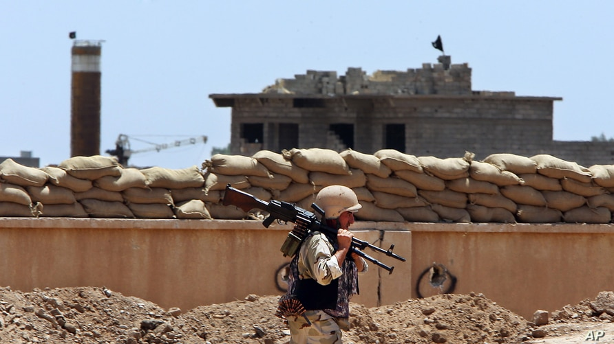 FILE - A Kurdish peshmerga fighter carries his weapon as he walks to his base where two Islamic State flags are seen on a building, right, and a water tower, left, south of Kirkuk, northern Iraq, June 25, 2014.