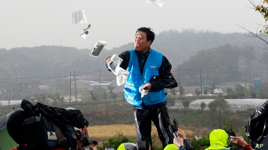 FILE - An activist hurls anti-North Korea leaflets as police block his planned rally on a road near the demilitarized zone in Paju, South Korea, Oct. 22, 2012.