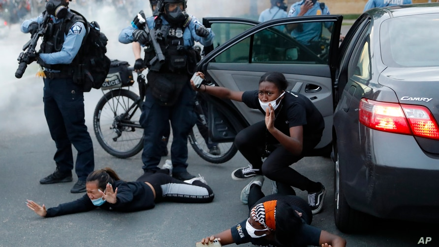 Police order motorists to the ground from their vehicle, May 31, 2020, during a protest in Minneapolis, Minnesota, over the death of George Floyd, a black man who died after a white police officer pressed a knee into his neck for several minutes.