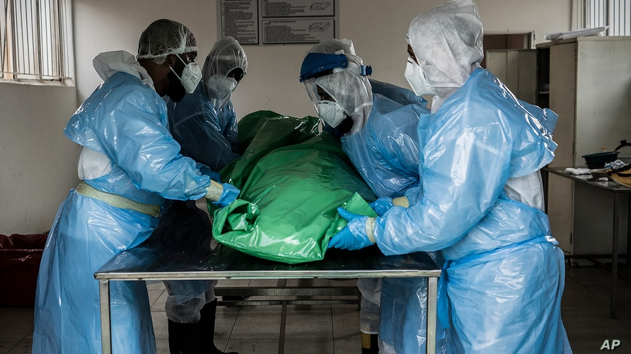 Members of a burial society prepare the body of a person who died from COVID-19, at the Avalon Cemetery in Lenasia, Johannesburg, South Africa, Dec. 26, 2020.