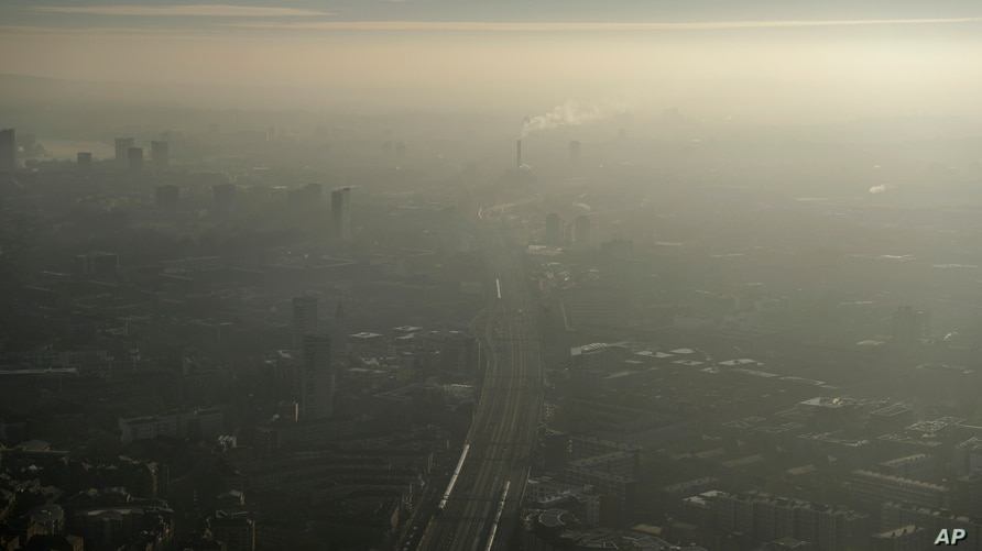 FILE - Pollution haze is seen over southeast London, through a window in a viewing area of the 95-story The Shard skyscraper, Jan. 19, 2017.