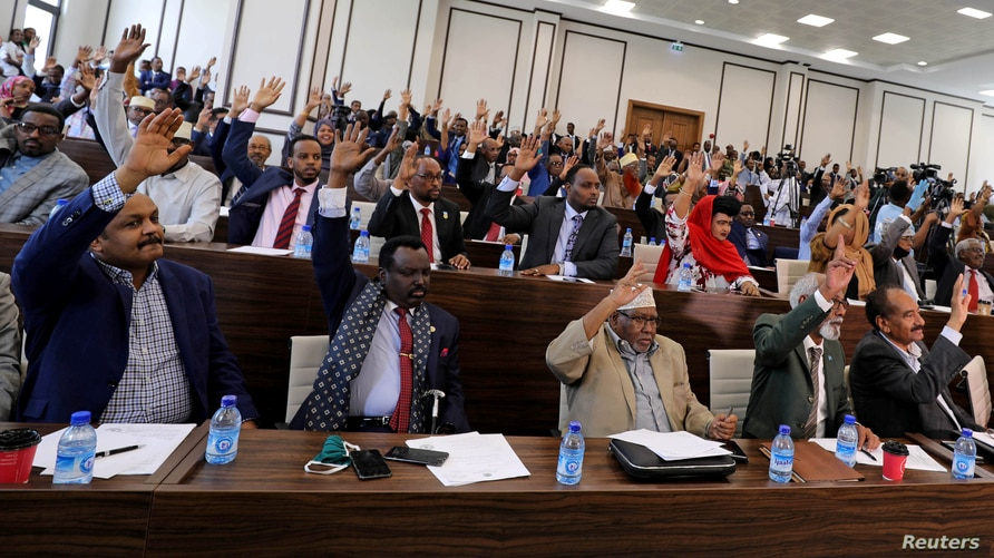 Somali parliament members raise their hands to approve the appointment of new Prime Minister Mohamed Hussein Roble, in Mogadishu, Sept. 23, 2020.