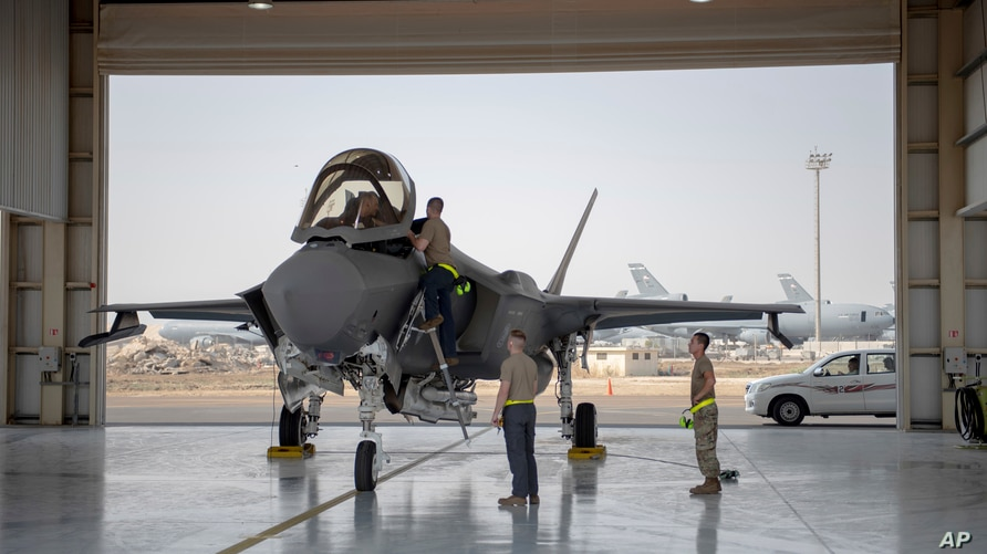 FILE - An F-35 fighter jet pilot and crew prepare for a mission at Al-Dhafra Air Base, UAE, Aug. 5, 2019.