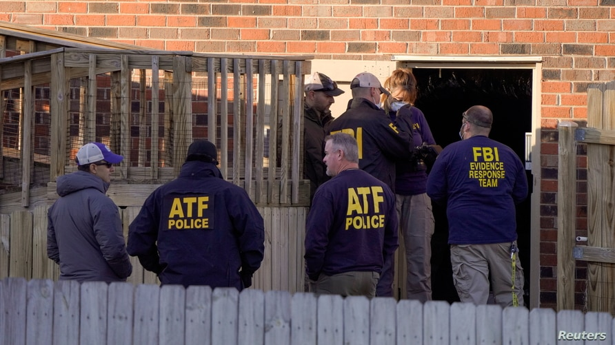 Law enforcement officers gather to investigate information arising the day after a downtown Nashville explosion, outside a duplex house in Antioch, Tennessee, Dec. 26, 2020.
