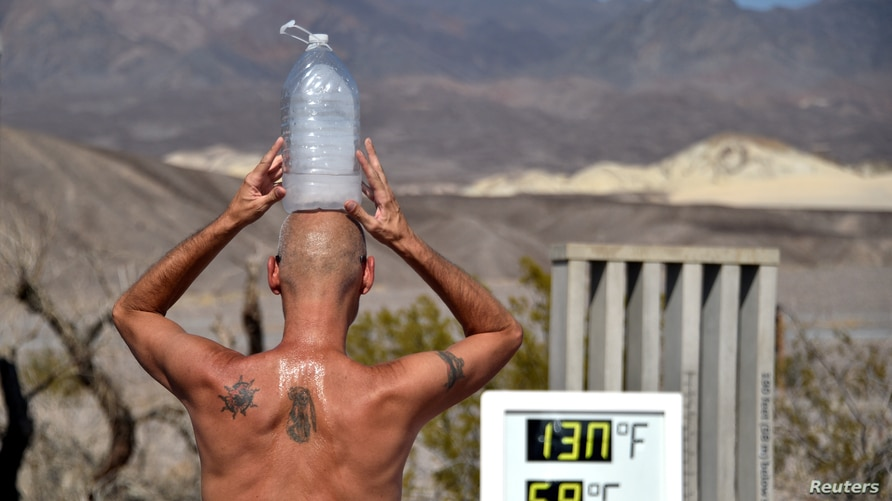 Steve Krofchik of Las Vegas keeps cool with a bottle of ice on his head as the unofficial thermometer reads 130° F (54.4° C) at the Furnace Creek Visitors Center in Death Valley, California, Aug. 17, 2020.