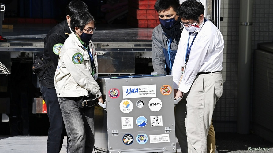 Japan Aerospace Exploration Agency's (JAXA) staff carry a case containing Hayabusa2's capsule with extensive samples of an asteroid as it arrives at JAXA Sagamihara Campus in Sagamihara in this photo taken by Kyodo, Dec. 8, 2020.