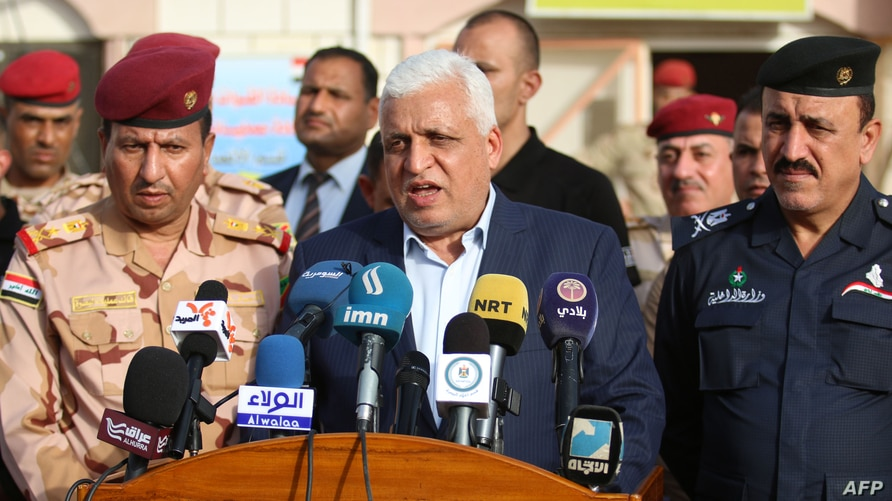 Falah al-Fayadh (C), Iraqi national security adviser and chief of the Hashed al-Shaabi (Popular Mobilisation Forces), gives a…