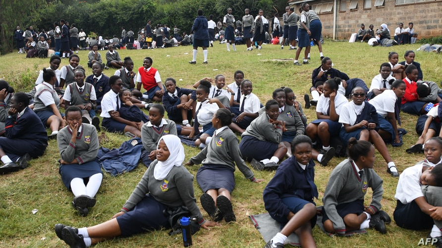 Students sit at the St. George's Girls' Secondary School compound as they wait to be picked by their parents and guardians …