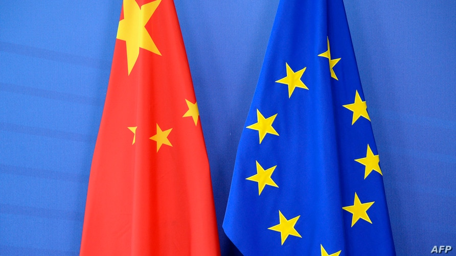 (FILES) In this file photograph taken on June 29, 2015, a Chinese flag (L) is draped beside the European Union (EU) flag during…