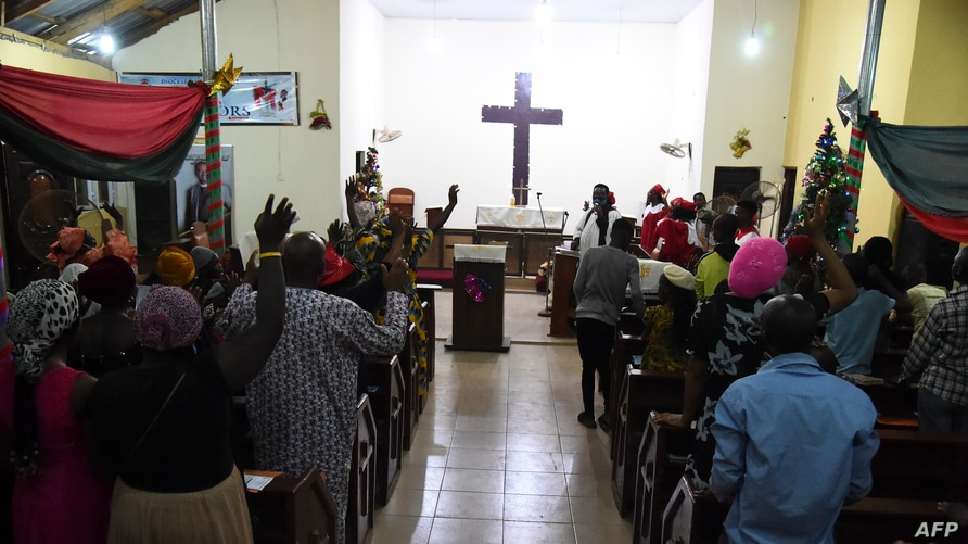 People dance to worship during a crossover night church service at the Anglican Church of Redemption Diocess of Lagos West,…