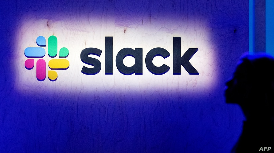 (FILES) In this file photo taken on April 24, 2019 an attendee walks by the company's logo during Slack's Frontiers conference…