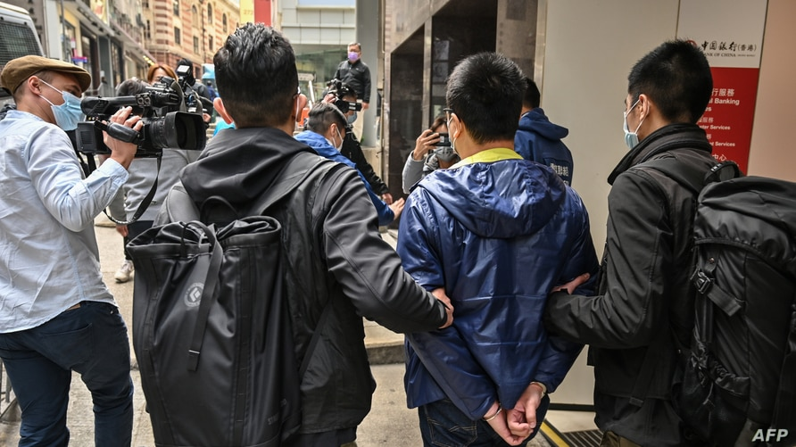 Ben Chung (2nd R) of a pro-democracy political group is arrested by police in the Central district after as many as 50 Hong…