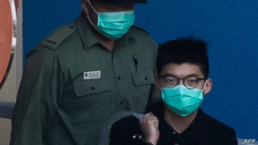 (FILES) In this file photo taken on December 18, 2020 pro-democracy activist Joshua Wong (R) leaves Lai Chi Kok Reception…