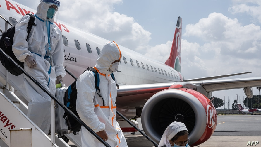 Passengers wearing full personal protective gears get off a plane at Jomo Kenyatta International Airport in Nairobi, Kenya, on January 19, 2021.
