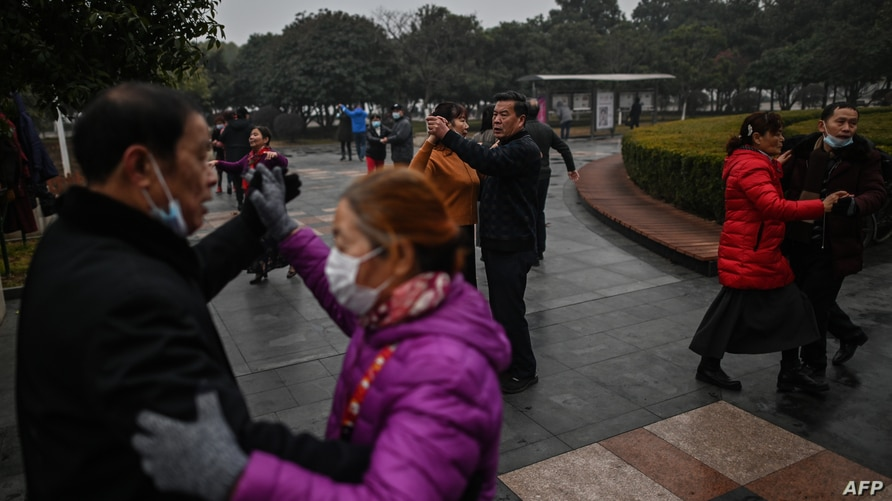 People dance in a park in Wuhan, China's central Hubei province on January 23, 2021. (Photo by Hector RETAMAL / AFP)